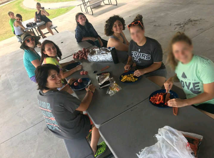 A group of youth practicing communication skills while making dinner.